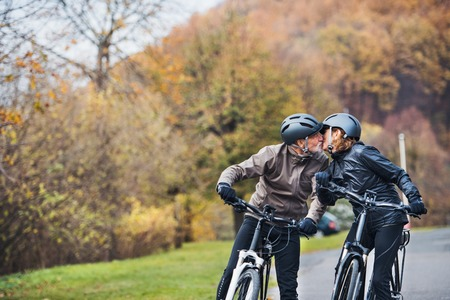 Active senior couple with electrobikes standing outdoors on a road in nature, kissing. Stock Photo - 115657696