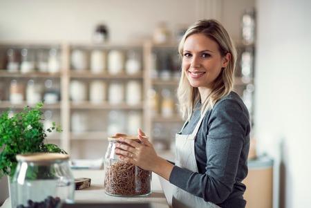 Een vrouwelijke winkelbediende in een zero waste-winkel, met een pot met boodschappen. Stockfoto