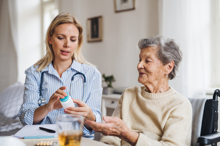 A health visitor explaining a senior woman in wheelchair how to take pills. Stockfoto