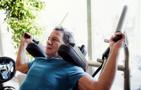 A senior man doing strength workout exercise in gym. Stok Fotoğraf - 115658183
