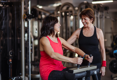 Two cheerful seniors women in gym doing strength workout exercise.