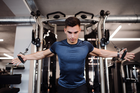 A young handsome man doing strength workout exercise in gym. Stok Fotoğraf