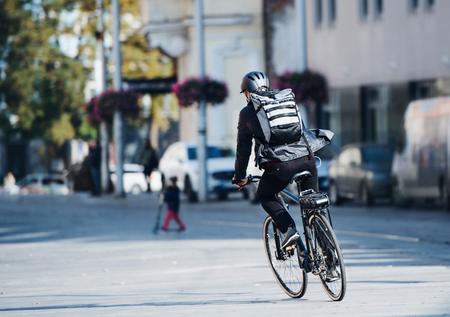 Una vista trasera del mensajero en bicicleta masculino entregando paquetes en la ciudad. Copie el espacio. Foto de archivo