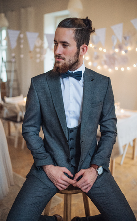 A handsome hipster young man with formal suit sitting on a stool on an indoor party. Stock Photo