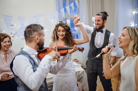 A young bride, groom and other guests dancing and singing on a wedding reception. Reklamní fotografie