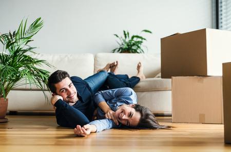 Una pareja joven con cajas de cartón que se mudan a una nueva casa. Foto de archivo