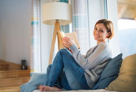 Młoda kobieta siedzi w pomieszczeniu na kanapie w domu, czytając książkę.