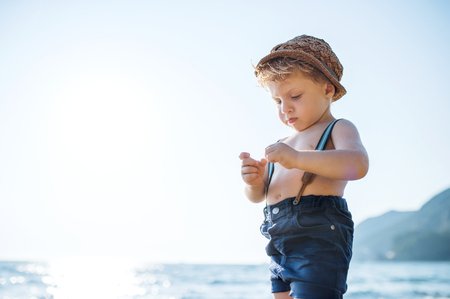 A small toddler boy with hat and shorts standing on beach on summer holiday. Stock Photo