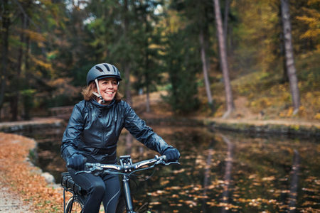 A senior woman with electrobike cycling outdoors on a road in park in autumn.