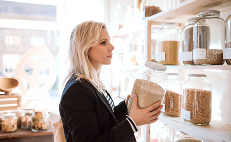 A young woman buying groceries in zero waste shop. Copy space.