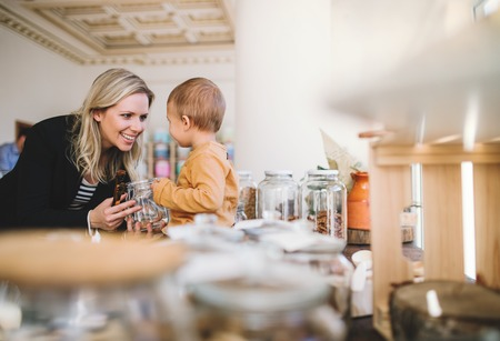 A young woman with a toddler boy buying groceries in zero waste shop. Stock Photo