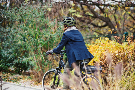 Unrecognizable active senior woman with electrobike cycling outdoors in park. Stock Photo