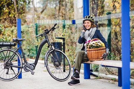 A senior woman with electrobike and flowers sitting on a bench outdoors in town.