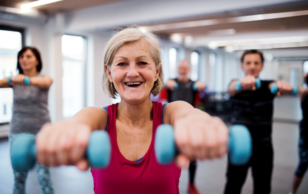 Group of cheerful seniors in gym doing exercise with dumbbells.