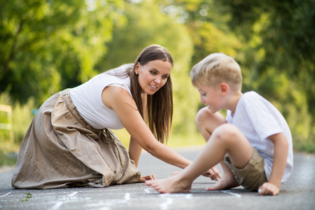 A small boy with mother drawing hopscotch on a road in park on a summer day. Stock Photo