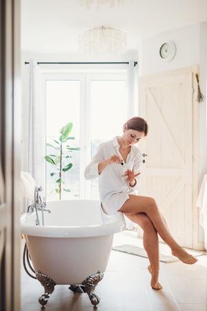 Una mujer joven por la mañana en un baño, aplicando esmalte de uñas. Foto de archivo