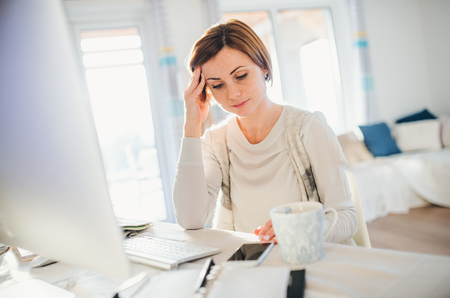 A tired young woman indoors, working in a home office. Stock Photo