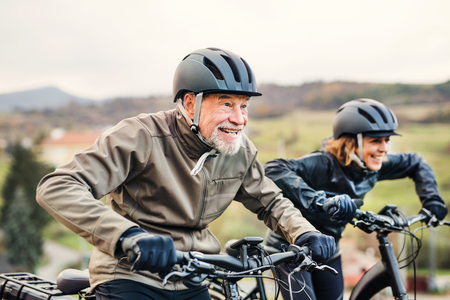Active senior couple with electrobikes cycling outdoors on a road in nature. Stock Photo