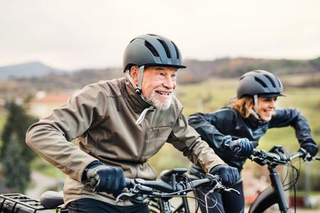 Aktives Seniorenpaar mit Elektrofahrrädern, die im Freien auf einer Straße in der Natur radeln.