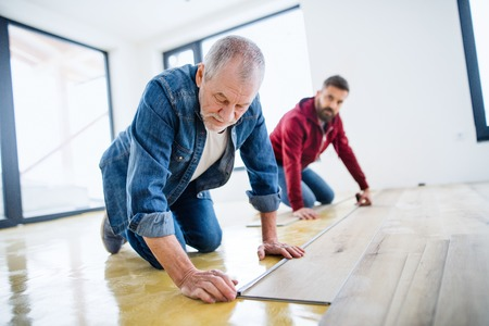 A mature man with his senior father laying vinyl flooring, a new home concept. Stockfoto