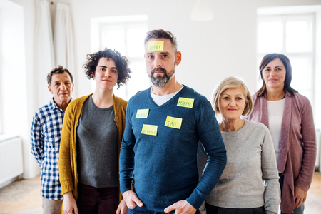 Young and old people standing with negative emotions adhesive notes during group therapy. Stock Photo