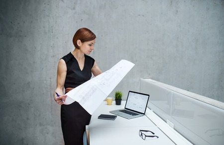 Young businesswoman or architect with blueprints and laptop standing in office.