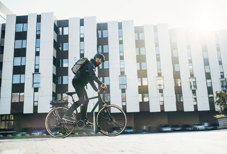 Male courier with bicycle delivering packages in city. Copy space. Stock Photo