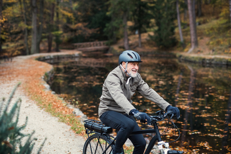 A senior man with electrobike cycling outdoors on a road in park in autumn. Stock Photo