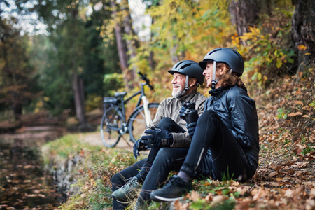 A senior couple with electrobikes sitting outdoors in park in autumn, resting.