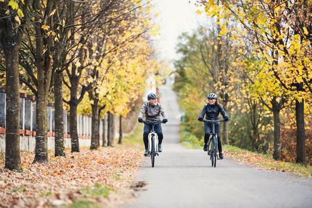 Un couple de personnes âgées avec des vélos électriques à vélo à l'extérieur sur une route. Banque d'images