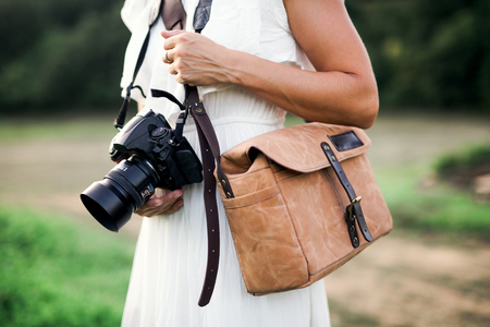 A midsection of woman in nature holding a camera and a brown leather bag. Stok Fotoğraf - 116647226