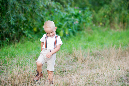 A cute cheeky small toddler boy in sunny summer nature. Copy space. Stock Photo