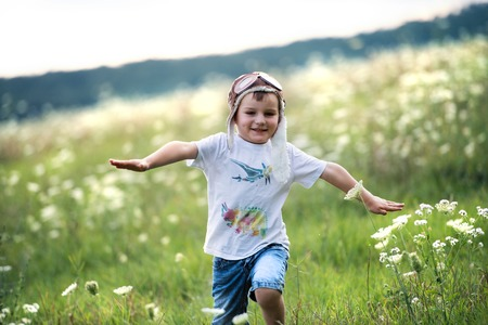 A small boy with pilot hat running in nature on a summer day. Imagens
