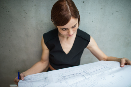 Young businesswoman or architect with blueprints standing in office. Banco de Imagens