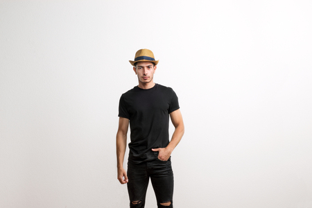 A confident hispanic young man with hat and black T-shirt in a studio. Stok Fotoğraf