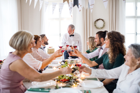 A big family sitting at a table on a indoor birthday party, clinking glasses. Stockfoto