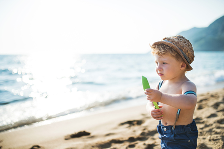A small toddler boy with hat and shorts standing on beach on summer holiday. Copy space. Stock Photo