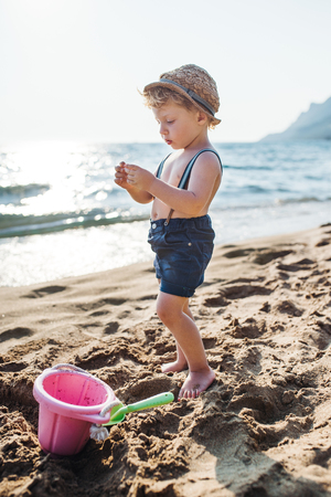 A small toddler boy standing on beach on summer holiday, playing.