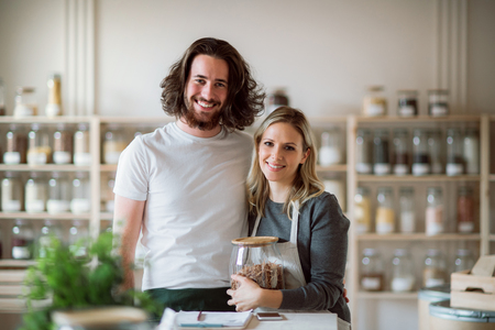 A portrait of two shop assistants standing in zero waste shop, looking at camera. Stock Photo