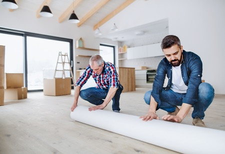 A senior man helping his son with furnishing new house, a new home concept. 写真素材