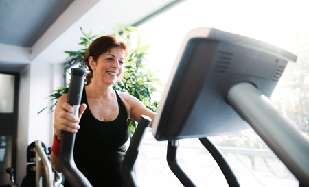 A cheerful female senior in gym doing cardio workout. 스톡 콘텐츠