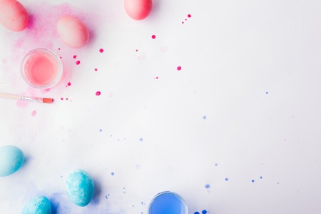 Eggs, paint and brush flat lay on a white background. Easter and spring composition. Stock Photo