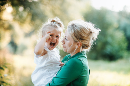 Young mother comforting crying small daughter in summer in nature. Standard-Bild