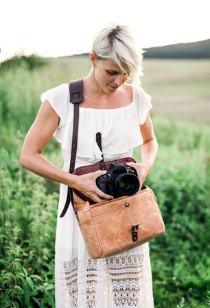 A front view of woman in nature taking out a camera from a brown leather bag.