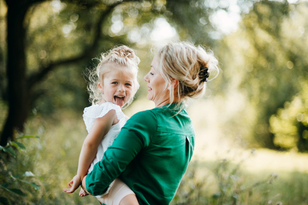 Young mother in nature with small daughter in the arms, having fun. Copy space.