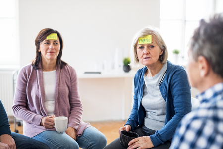 Men and women sitting in a circle during group therapy, adhesive notes on forehead.
