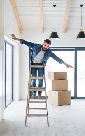A mature man with cardboard boxes standing on a ladder, furnishing new house.