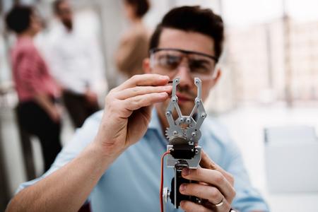 Un jeune homme d'affaires ou scientifique avec une main robotique debout au bureau, travaillant. Banque d'images