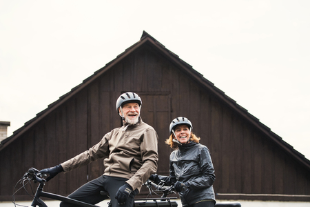 Active senior couple with electrobikes standing outdoors in front of a house.
