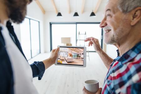 Un uomo anziano che aiuta suo figlio ad arredare una nuova casa, un nuovo concetto di casa. Archivio Fotografico